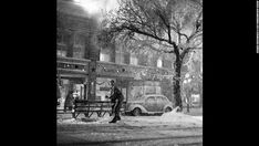 """1946-""""Its a Wonderful Life,"""" black and white photo of Jimmy Stewart as he enjoys the falling """"snow"""" in downtown Bedford Falls, the fictional town in the classic American Christmas movie."""