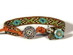 Bead Loom leather wrap bracelet in light olive green, turquoise and brown with silver  This bracelet is made with 11/0 seed beads on golden brown naturally dyed USA leather cord.  The button is pewter Celtic design.  Two Czech flower dangles.  All Aerieanna bracelets are designed to