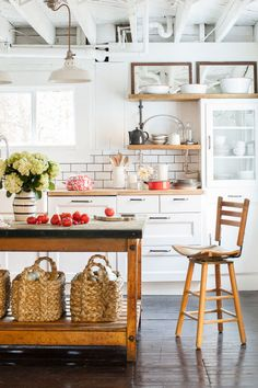 This kitchen makeover was inexpensive thanks to subway tiles and plenty of white paint, and a few bargains like Ikea cabinets, butcher-block countertops, and farmhouse sink. An antique bakery table, equipped with Pottery Barn baskets, functions as the kitchen island.