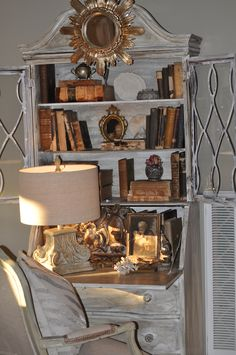 Pretty display - warm antique books & gilt against chalky, white-washed secretary - Andrea McLaughlin
