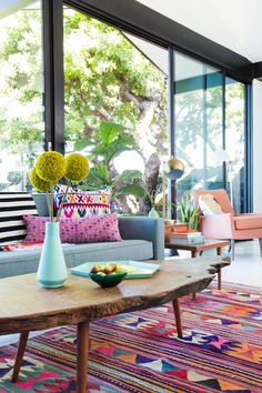 dream home | living room - colorful pattern rug + pillows w/ large windows for natural light - via Emily Henderson