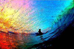 Preciosa ola de surf en medio del arco iris