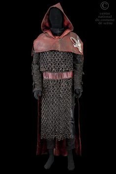 The Bishop of Ely..Doublet and breeches and black lurex quilted plaid metal eyelets. Trimmed with black leather sleeves legs, steel buckles. Low breeches laced Lurex and black leather. Tabar red brown leather and plastic chains. Cape red brown leather cap trimmed with a silver unicorn head resin on the left shoulder.