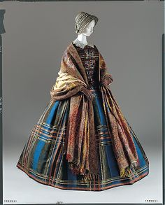 Plaid silk dress, pleated; European, ca 1857. Shown with lace collar, colored gloves, modest bonnet, shawl.
