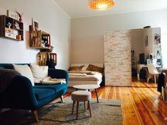 Stylisches WG-Zimmer mit blauer Couch, Regalen aus Weinkisten und Dielenboden.