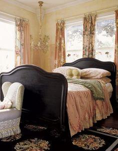 Black bed frame is ingenious in this feminine room.