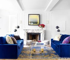 Bold blue sofas in white living room with gorgeous marble fireplace and modern furniture