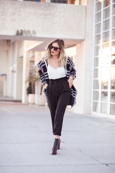 White lace cami+black high-waist pants+dark brown booties+cheched fringed cardigan+sunglasses+white chain shoulder bag. Fall Casual Outfit 2017
