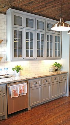 Gray cabinets and oak hardwood floors. Kitchen inspiration with glass upper cabinets and white subway tile backsplash. Industrial kitchen pendant