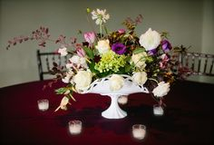 A free flowing, cascading arrangement in a antique milk glass vase, using viburnum, purple anemones, hot pink tulips, white roses, white ranunculus, scabiosa, and colorful seasonal foliage, surrounded by white candle votives. A wedding reception held at The Calcasieu Restaurant in New Orleans.