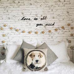 Minha cama com almofadas em tons de branco e cinza. Parede com papel de parede de tijolinhos e fio de luz com bolas douradas simulando uma cabeceira.
