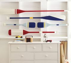 Buy/find some oars and paint them orange and blue for wall decor. Keep part of the original wood color exposed.