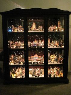 Christmas village displayed in a curio cabinet with led mini lights for stars Christmas Village Decorations, Halloween Village Display, Lemax Christmas Village, Christmas Houses, Christmas Villages, Christmas Presents, Winter Christmas, Christmas Holidays, Christmas Ornaments