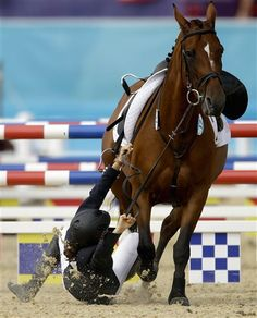 Tamara Vega, of Mexico, falls off her horse Douce de Roulad, during the equestrian show jumping stage of the women's modern pentathlon at the 2012 Summer Olympics, Sunday, Aug. 12, 2012, in London. (AP Photo/David Goldman)
