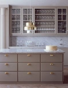 pale gray cabinets, brass hardware and marble countertops. by lupe