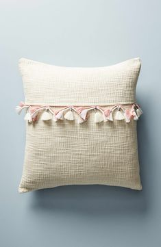 Wrapped tassels add a dash of textural intrigue to this woven accent pillow