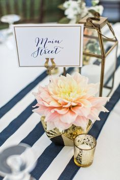 Preppy navy blue + light pink centerpiece idea - navy blue + white striped table runner with gold mercury vase filled with a light pink dahlia + mercury candle holders + gold lantern - tables names are locations special to the bride + groom {Flora + Fauna}