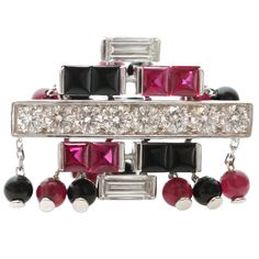 Inspired by the fusion of Chinese culture and Art Deco design, this fabulous ring from Cartier's Le Baiser Du Dragon collection is made in 18k white gold and features red rubies and black onyx, cut as cabochon beads and faceted square-cut stones. Accented by sparkling round and baguette-cut diamonds. Circa 2003.