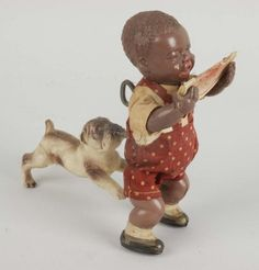 Celluloid toy of a watermelon eating little boy being chased by a dog. (So many Black related toys are disparaging-this one is an example)