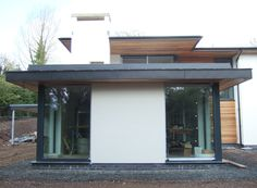 Contemporary House design Antrim, Northern Ireland, with zinc roof, white render, stonework and cedar cladding