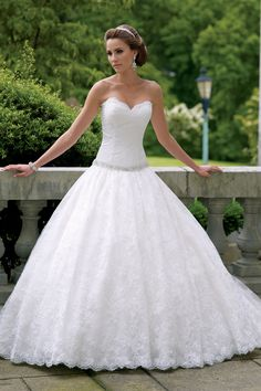 Strapless lace over taffeta ball gown wedding dress with scalloped sweetheart neckline, corded lace bodice features intricate hand-beaded jeweled dropped waistband, gathered full skirt with scalloped hemline spilling into chapel length train. Available in Ivory/Dark Ivory and White.
