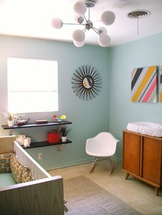 mid century...need the sun mirror! I love the light fixture, the table turned into a changing table, and I think it is so funny there is a vent right above the changing table! :)
