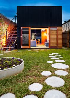 10 Landscaping Ideas For Using Stepping Stones In Your Garden // Round stepping stones scattered throughout the yard of this home create paths and fun places to practice your hopping skills.