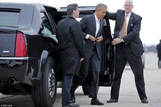 Obama buttons up his suit jacket as he steps out of his motorcade and onto the tarmac at Andrews Air Force Base