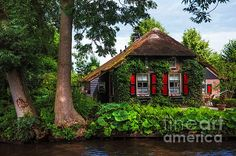 Idyllic Village. Venice of the North by Jenny Rainbow. Giethoorn, also known as the Venice of Holland or theVenice of the North, is a beautiful village in the Netherlands. There are no cars or roads here. #PrintSales #Netherlands #Giethoorn #House #FairytaleHouse #FineArtPrints #Garden #Dream #JennyRainbowFineArtPhotography #Travel #Holland #Dutch #Architecture #Boat #Channel #Canal #Europe #Idyll #IdyllicVillage
