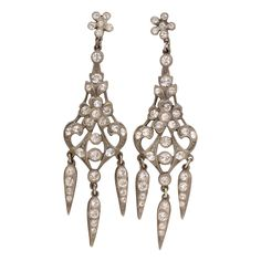 Dramatic Edwardian Style Chandelier Earrings.  The mountings are of sterling silver and fully articulated for maximum effect in the chandelier style. The body is composed of garland and foliate shapes with three fox tail pendants.    The sparkle is provided by white paste.    Paste is a kind of leaded glass that is cut and polished as a gem would be.  It was invented by a French jewelry designer in 1724.