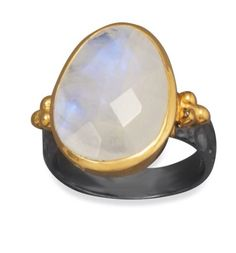 Natural Moonstone on 14k gold setting with gun barrel metal ring band.  Yes it's unique and beautiful!