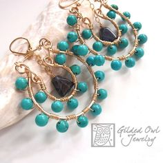 Picture Yourself in these Exotic gold and sky blue turquoise earrings with dark blue sodalite gemstones as accent beads that dangle in the horseshoe center. Handmade by @Gilded Owl Jewelry