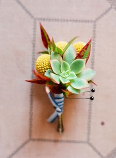 Succulent boutonniere with yellow crespedia, and foliage