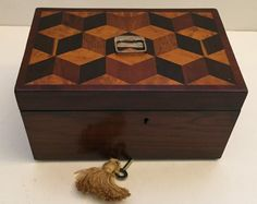 Unusual Tea Caddy, c.1820 // Very unusual Tea Caddy, c.1820. The box is made from Rosewood, it has a lovely brass Tumbling block design to the top made from various woods and cross banded in Mahogany. What makes this box different can be found when opening the Caddy to reveal the unusual set with one compartment bigger than the other. To the front of the box you will find the key hole off centre in its original state. // Price £270 //  - Maria Elena Garcia -  ► www.pinterest.com/megardel/ ◀︎