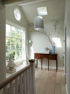 Very simple decor makes for a beautiful hallway.  Love the ceiling height, skylight and windows.