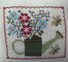 This 5 x 5 1/2 mini pillow will be great for your spring and summer decor. This mini pillow is stitched on 32 count lambswool linen, backed with beige cotton blend fabric, and stuffed with polyfil. A watering can with pretty blue, red, and purple flowers make a pretty garden themed
