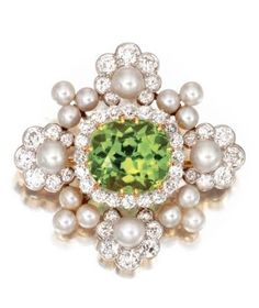 Platinum, Gold, Peridot, Pearl and Diamond Brooch, Circa 1890. Set in the centre with a cushion-shaped peridot weighing approximately 9.50 carats, framed by old European-cut diamonds weighing approximately 2.60 carats, and pearls measuring approximately 4.8 to 3.6 mm., signed Tiffany & Co.