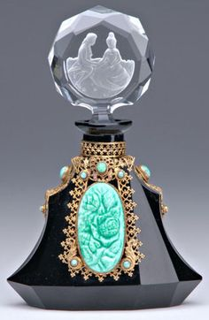 A Czechoslovakian Glass Perfume Bottle, Black crystal with jeweled metalwork, seated lovers stopper, circa 1920's