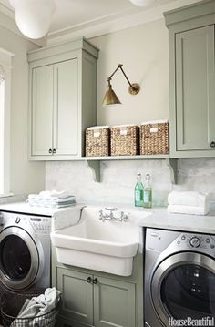 In the laundry room, think beyond the basic white color schemes and add some accent colors, decorative storage, and subtle art.