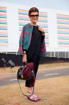 Street style look preto com bomber jacket colorida e sandália roxa.