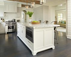 Gorgeous transitional kitchen boasting dark stained oak wood floors showcases a large light gray kitchen island fitted with a stainless steel microwave and storage cabinets  topped with Super White Quartzite countertops seating three Tolix Barstools illuminated by three seeded glass light pendants hung from a ceiling accented with rustic wood beams.