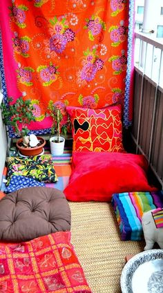 Boho Chic Balcony with Flower Patterned Fabrics, Red Cushions and Plants