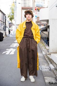 Vintage fashion-loving Kyohei on the street in Harajuku wearing a Puma trech coat over a resale top, Edwina Horl pants, sneakers, and Issey Miyake accessories. Full Look