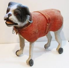 Dog Pull Toy-a fabulous paper mache and wood dog pull toy--body covered in white flannel--face painted--glass eyes--original tin wheels--red felt blanket coat--leatherette collar--just wonderful in every way.