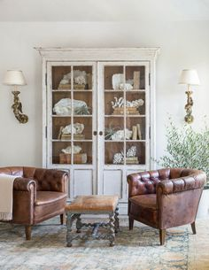 brown leather chesterfield style club chairs. love the vintage farm house cabinet painted white.