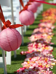 Ceremony decor - Paper lanterns hanging from the chairs and flower petals lining the aisle.