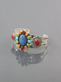 Cluster bracelet on stamped split bracelet band with a large denim lapis center stone surrounded with stones in red coral, spiney oyster, gaspeite and turquoise. This cluster bracelet is embellished with stamped side pieces set with red coral and it measurers 1 3/8 inches wide at the center.