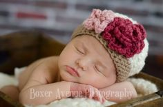 This little girl hat is made from cream yarn and feature a brown bottom. The hat also feature two flowers. The rose style flower is made from a