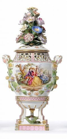 A Carl Thieme Encrusted Porcelain Pot Pourri Vase and Cover, circa 1870, the pierced and gently domed cover with An elaborate finial as A spray of flowers, on inswept fan pierced shoulders, veiled maiden mask side handles over encrusted fruits and flowers, the front and reverse painted with couples in 18th century costume dallying, on angular tripod legs linked by laurel swags and on A tri-concave flat plinth, blue painted crossed swords mark and T, 37.5cm See illustration