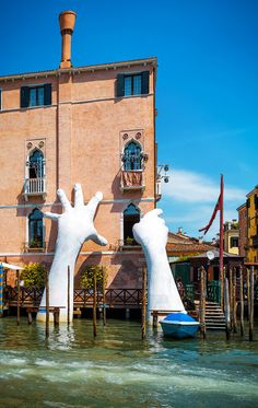 Grand Canal in Venice, Italy. Giant hands - sculpture by Lorenzo Quinn.